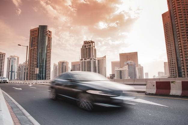 Auto's met hoge gebouwen bij de zonsondergangachtergrond