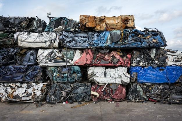 Auto's op autokerkhof, geperst en verpakt voor recycling.