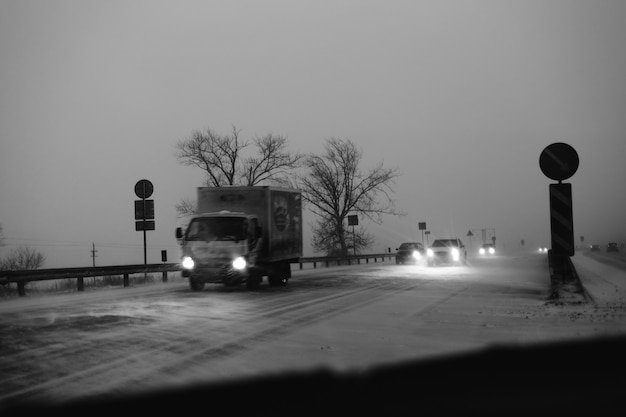 Auto's rijden 's avonds op de snelweg tijdens een sneeuwstorm.