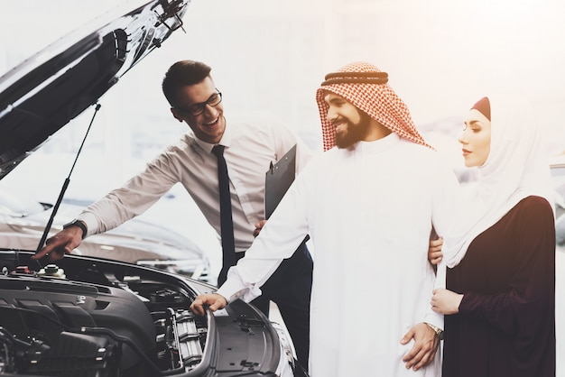 Auto salon family in muslim clothing and dealer