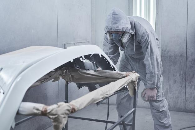 Auto schilderen en auto reparatie service. automonteur in witte overall schildert auto met airbrush-pulverizer in verfkamer