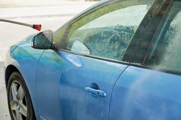 Auto schoonmaken met water onder hoge druk bij wasstraat