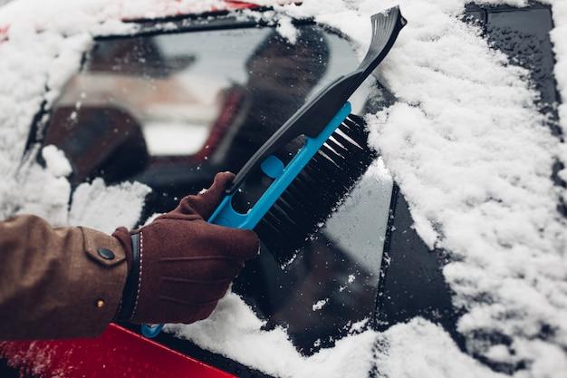 Auto schoonmaken van sneeuw met bezem. mens die automobiel venster behandelen die ijs met borstel in openlucht verwijderen