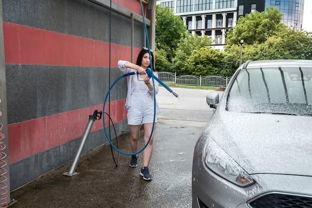 Auto schoonmaken. vrouw wassen houw auto met schuim. professioneel