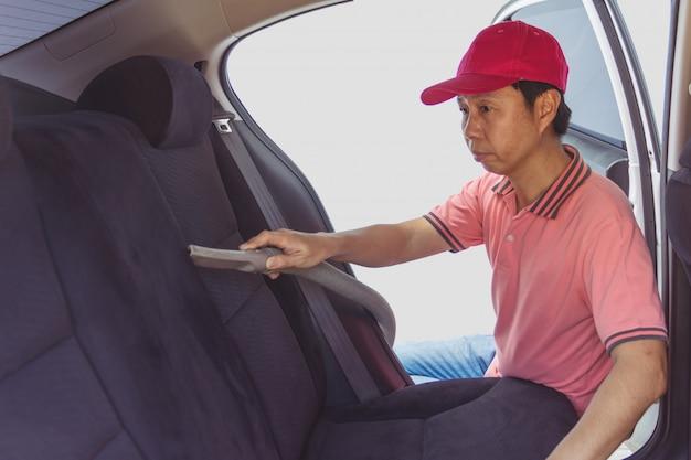 Auto service personeel reiniging van interieur van de auto met stofzuiger
