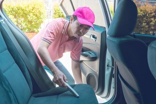 Auto service personeel schoonmaken van het interieur van de auto met een stofzuiger