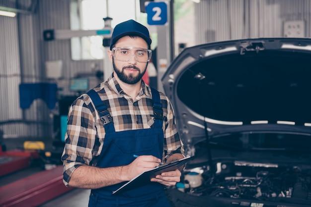 Auto service reparatie onderhoud automonteur man in veiligheid uniform met klembord