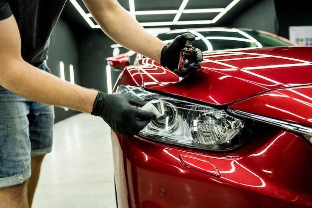 Auto service werknemer nano coating toe te passen op een auto-detail.