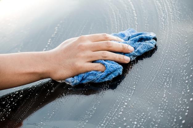 Auto servicepersoneel reiniging auto achter voorruit
