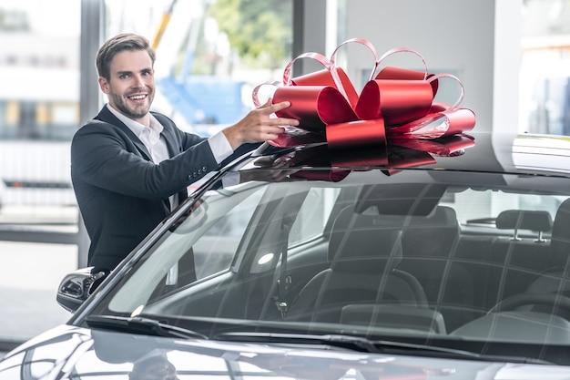 Auto showroom. aantrekkelijke vrolijke jonge man in formeel pak in de buurt van nieuwe auto met grote rode strik op dak bij dealer