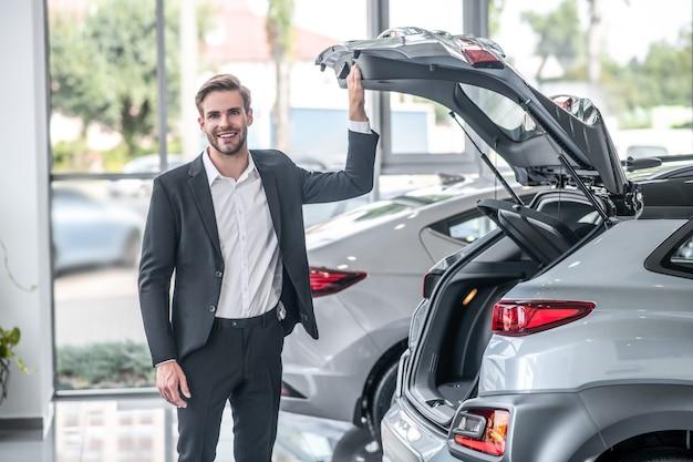 Auto showroom. jonge volwassen glimlachende aantrekkelijke man in een donker pak die overdag in de buurt van de open kofferbak van de auto in de salon staat