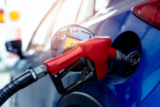 Auto tanken bij tankstation. vul brandstof bij en vul benzine bij. benzinepomp brandstof mondstuk vullen in brandstoftank van auto bij tankstation.