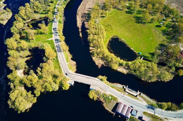 Auto verplaatsen op de brug over de rivier in europese stad, luchtfoto. vogelperspectief van het landschap van de kleine stad
