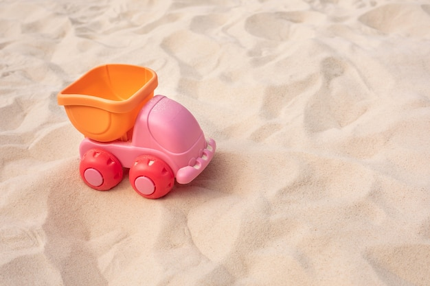 Auto, vrachtwagenstuk speelgoed op zand, strandzomer en leerconcepten