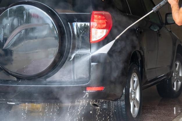 Auto wassen. auto schoonmaken met water onder hoge druk en schuim