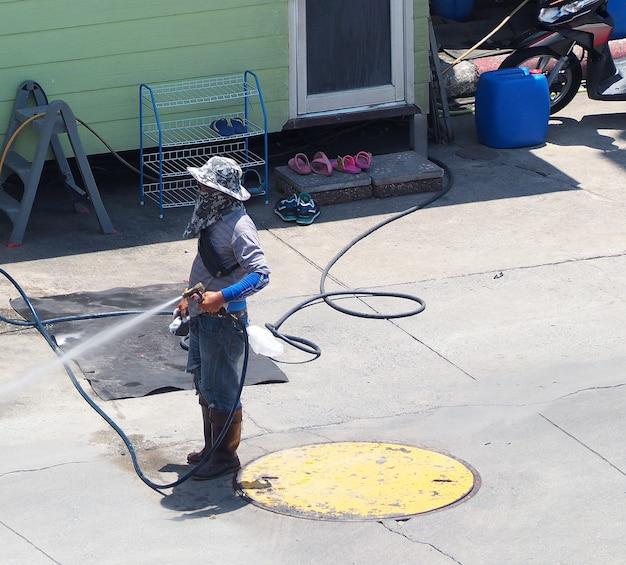 Auto wassen door werknemer die buiten staat met schonere waterstraal en overdag.
