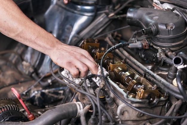 Auto werktuigkundige die aan motor van een auto bij de reparatiedienst werkt. sluit omhoog mening.