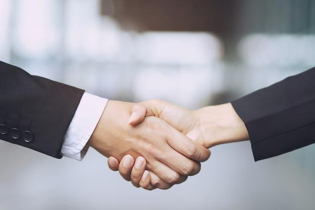 Auto-zaken. close up van een zaken man dealer auto aanbieden aan nieuwe eigenaar en hand schudden tussen twee felicitaties aan klanten. filtertoon buiten zonnig in de ochtend.