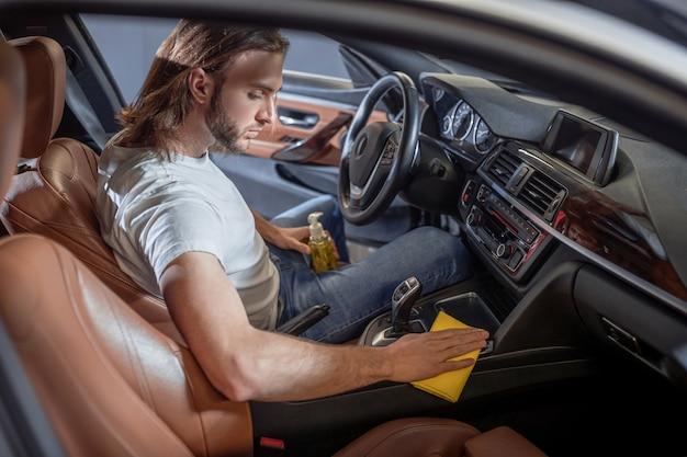 Auto zorg. jonge, bebaarde ernstige enthousiaste man zorgvuldig afvegen van oppervlakken zittend in de auto in de bestuurdersstoel