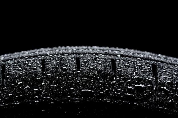 Autoband bedekt met waterdruppels op zwart