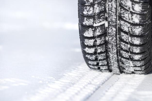 Autoband in de winter op de weg die met sneeuw wordt behandeld