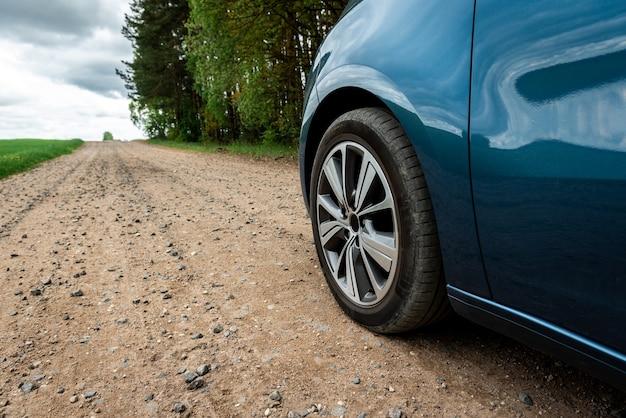 Autoband op onverharde weg dichtbij veld.