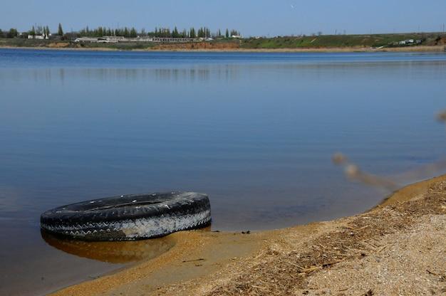 Autobanden op de wal hadzhibeysky estuarium. eutrofiëring van het reservoir, het probleem van de ecologie