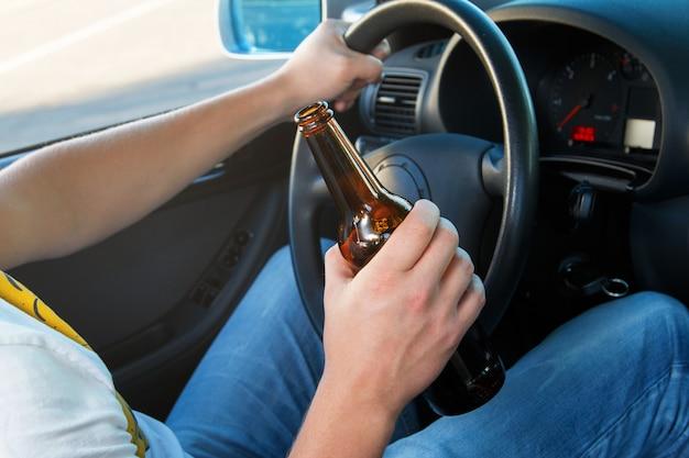 Autobestuurder die een fles bier houdt