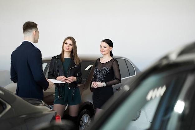 Autobusiness, autoverkoop - een paar vrienden van meisjes met een autodealer kiezen een auto bij een autodealer