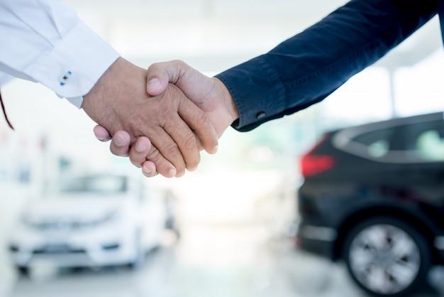 Autobusiness, autoverkoop, overeenkomst, gebaar en mensenconcept - sluit omhoog van dealer die sleutel geven aan nieuwe eigenaar en handen schudden in autoshow of salon