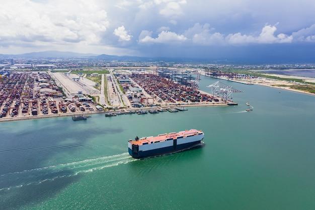 Autocarrier die op het groene overzees en de internationale verschepende van de containerhaven luchtmening als achtergrond varen