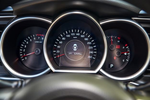 Autodashboard met rode achtergrondverlichting: kilometerteller, snelheidsmeter, toerenteller, brandstofniveau, watertemperatuur en meer.