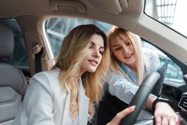 Autodealer-adviseur die het interieur van de auto aan een klant toont
