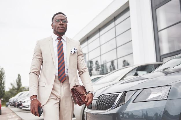 Autodealer bezoeken. casual zwarte zakenman in een pak in de buurt van de auto.