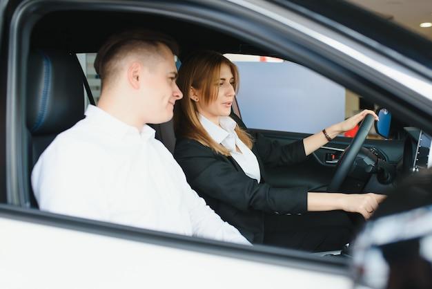 Autodealer bezoeken. het mooie paar bekijkt camera en glimlacht zittend in hun nieuwe auto