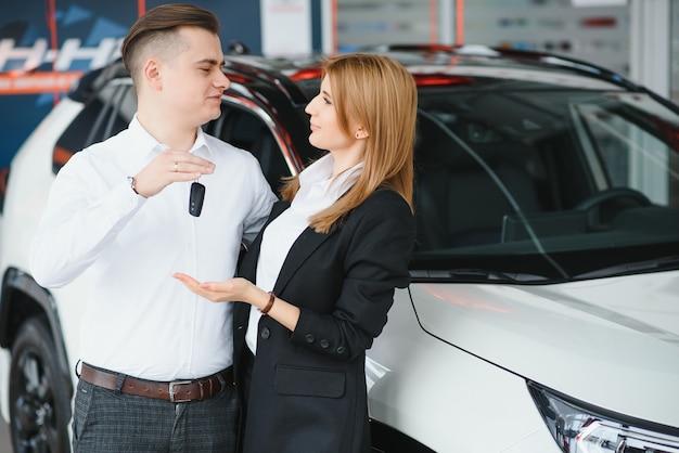 Autodealer bezoeken. het mooie paar houdt een sleutel van hun nieuwe auto vast en glimlachend, kust het meisje haar echtgenoot op de wang