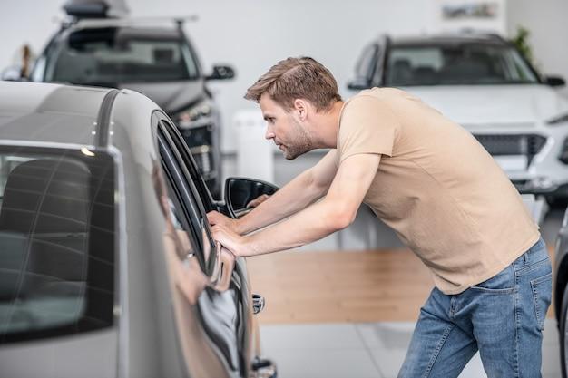 Autodealer. donkerharige blanke jongeman die geïnteresseerd auto in de dealer onderzoekt en met zijn handen verlaagd glas aanraakt
