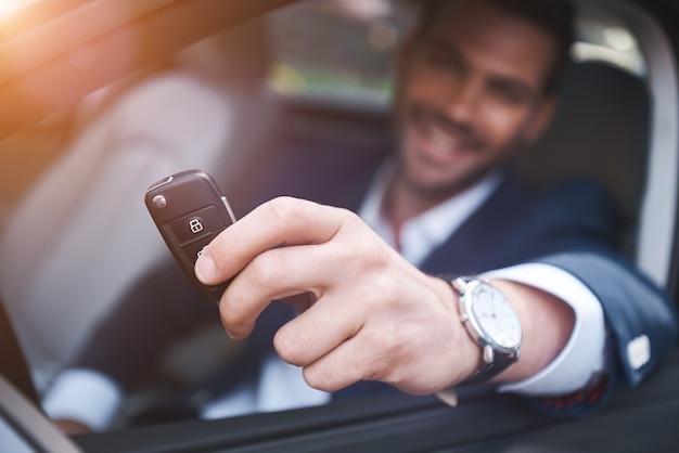 Autodealer jonge man die autosleutel ontvangt van verkoopster