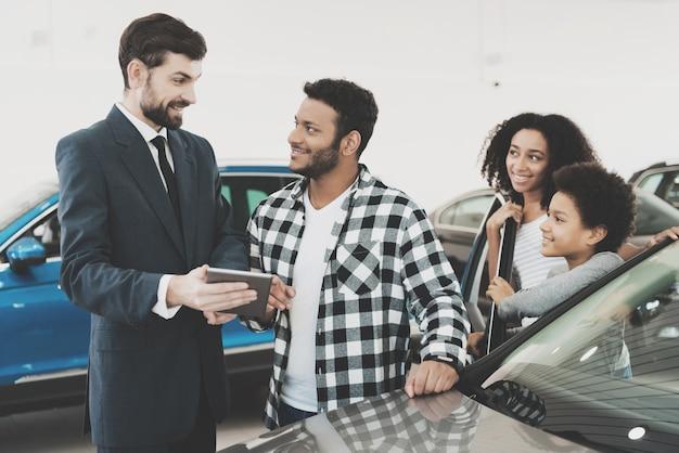 Autodealer met tablet praat met klanten.