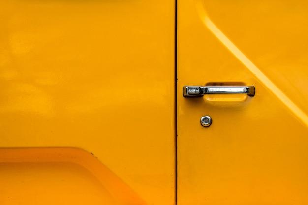 Autodeurhandvat bij gele vrachtwagen