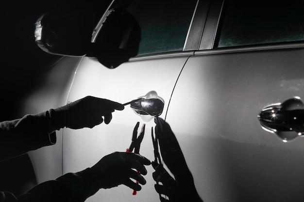 Autodief die een gereedschap gebruikt om in een auto in te breken