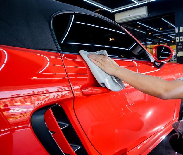 Autodienst werknemer polijsten auto met microfiber doek.