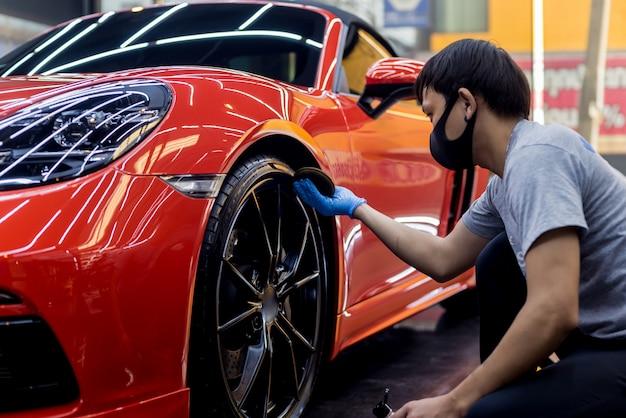 Autodienstmedewerker die autowielen oppoetst met microvezeldoek.