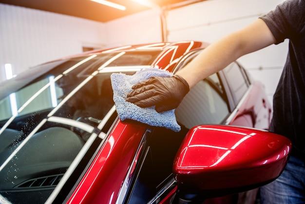 Autodienstmedewerker polijst auto met microvezeldoek.