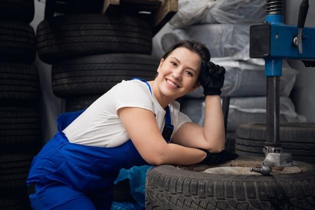 Autodienstmedewerker poseren naast wielen en een werktuigmachine