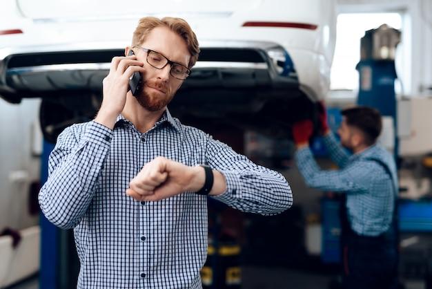 Autoeigenaar die aan de telefoon spreken. servicestation.