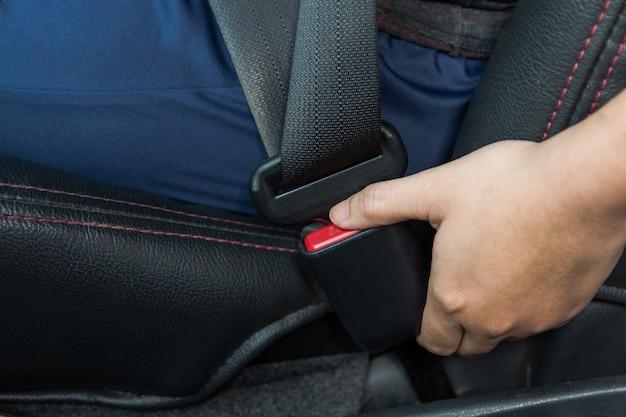 Autogordel. vrouw maakt de veiligheidsgordel vast aan de auto veilig rijden. veiligheidsgordel in de hand.