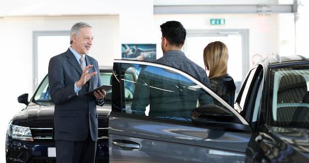 Autohandelaar die de eigenschappen van een auto aan een paar exaplining door een digitale tablet te gebruiken