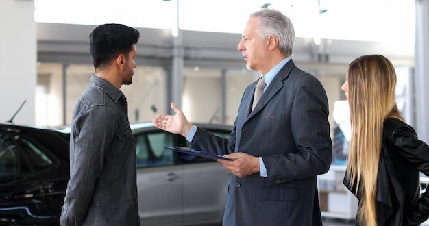Autohandelaar die de eigenschappen van een auto aan een paar exaplining door een document te lezen