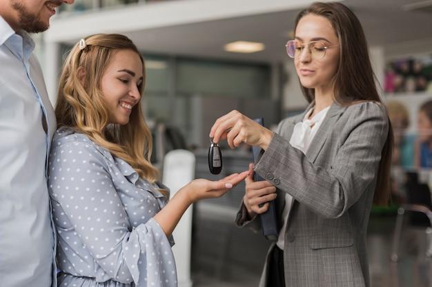 Autohandelaar die sleutels geeft aan een glimlachende vrouw